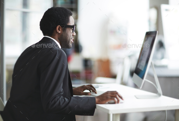 Businessman by computer - Stock Photo - Images