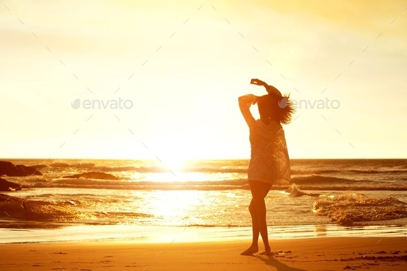 Silhouette young woman walking on beach during sunset - Stock Photo - Images