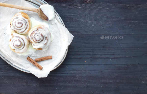 Cinnamon rolls with cream-cheese icing and cinnamon sticks on a - Stock Photo - Images