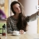 Young Beautiful Girl Makes Selfie In a Cafe After Fruit Tea - VideoHive Item for Sale