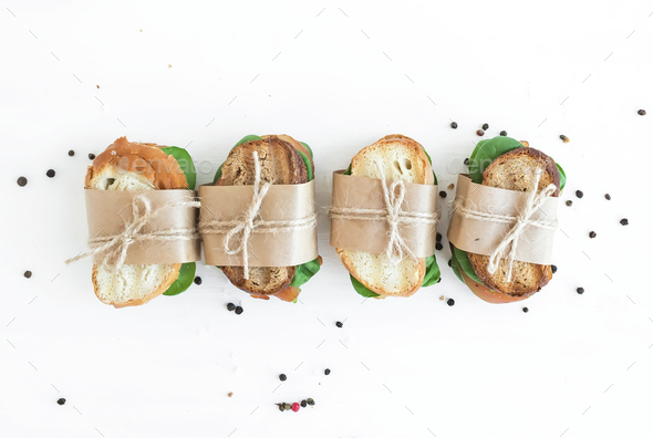 Chicken and spinach sandwiches wrapped in craft paper over a whi - Stock Photo - Images