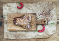 Cooked meat t-bone steak on serving board with red chili peppers