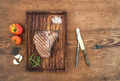 Cooked meat t-bone steak on serving board with garlic cloves, tomatoes