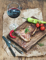 Cooked meat t-bone steak on serving board with roasted tomatoes