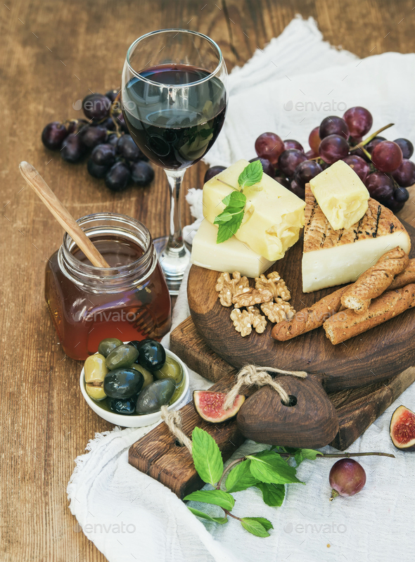 Glass of red wine, cheese board, grapes, fig, strawberries, honey and bread sticks - Stock Photo - Images