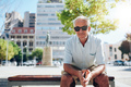 Handsome senior man sitting outdoors in the city - PhotoDune Item for Sale