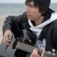 Young Man Playing The Acoustic Guitar At The Beach