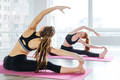 Two women doing stretching exercises in yoga center