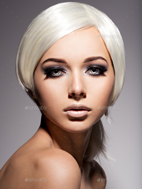 Fashion portrait of young woman with blond hairs and black make - Stock Photo - Images
