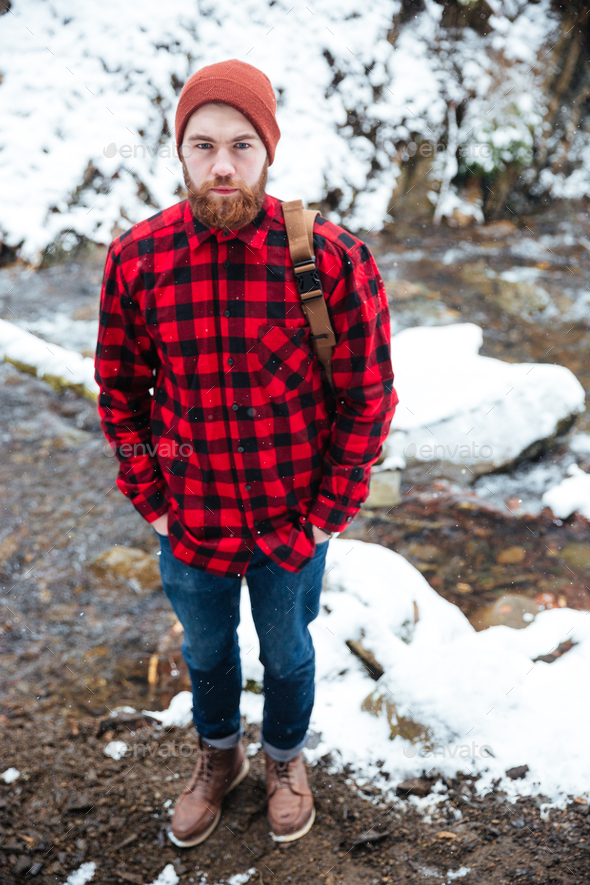 Man with backpack standing in winter forest near mountain river - Stock Photo - Images