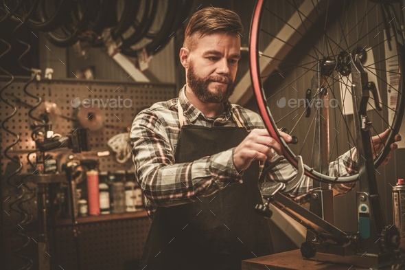 Stylish bicycle mechanic doing his professional work in workshop. - Stock Photo - Images