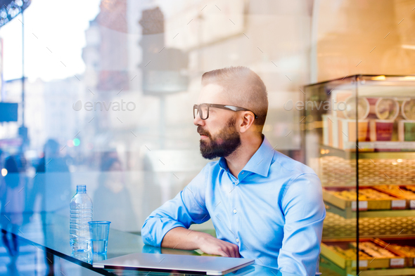 Manager sitting in cafe by the window, drinking water - Stock Photo - Images