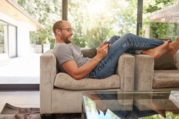 Man Relaxing On Sofa Using Tablet Pc Stock Photo Images