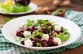Salad of baked beets, arugula, cheese and nuts