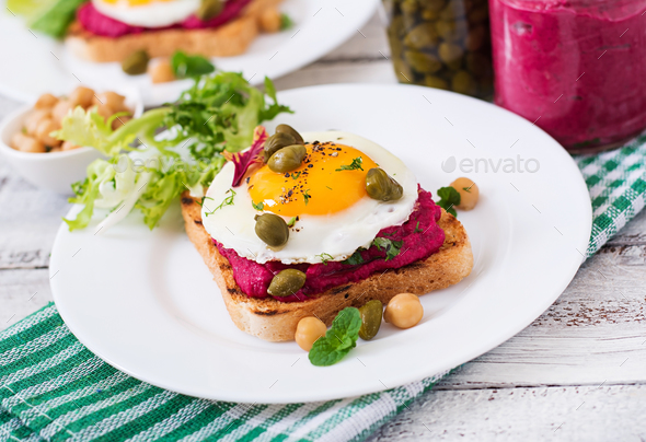 Diet sandwiches with beet root hummus, capers and egg - Stock Photo - Images