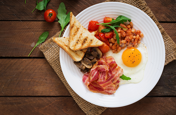 English breakfast - fried egg, beans, tomatoes, mushrooms, bacon and toast. Top view - Stock Photo - Images