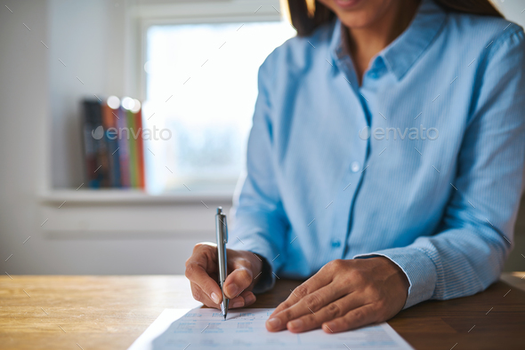 Businesswoman writing on a document - Stock Photo - Images