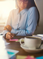 Female entrepreneur writing notes at desk - PhotoDune Item for Sale
