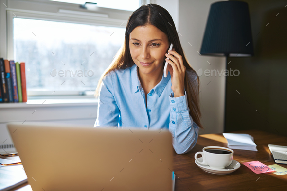 Cheerful young adult business owner on phone - Stock Photo - Images
