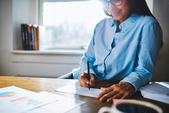 Cheerful woman writing at desk - Stock Photo - Images
