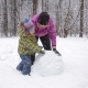 Mother And Young Son Make a Snowman In Winter Park - VideoHive Item for Sale