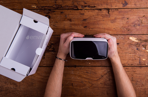 Hands of man holding virtual reality goggles, wooden table - Stock Photo - Images