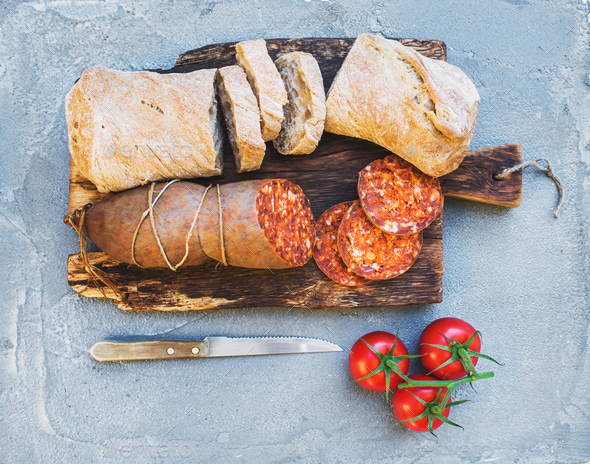 Wine snack set. Hungarian mangalica pork salami sausage, rustic bread and fresh tomatoes - Stock Photo - Images