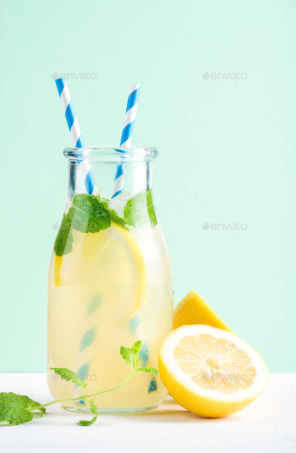 Bottle of homemade lemonade with mint, ice, lemons, paper straws and pastel blue background - Stock Photo - Images