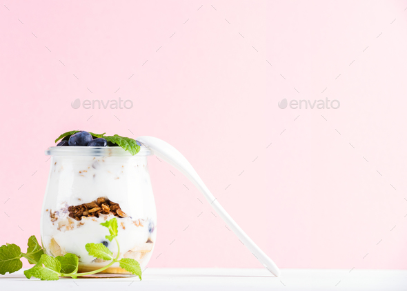 Yogurt oat granola with jam, blueberries and green leaves in glass jar on pink pastel backdrop - Stock Photo - Images