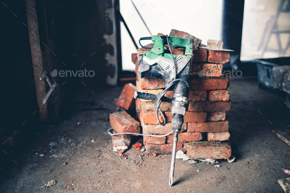 Construction tool, industrial jackhammer with demolition debris and bricks - Stock Photo - Images