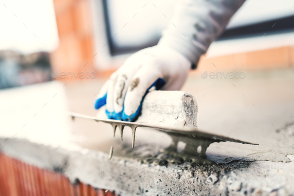construction worker using steel trowel for plastering - Stock Photo - Images