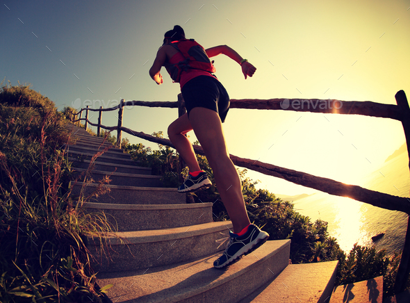 Woman runner trail running on seaside mountain stairs, training for cross country running. - Stock Photo - Images