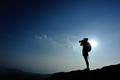 Woman photographer on sunset mountain peak - PhotoDune Item for Sale