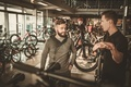 Salesman showing a new bicycle to interested customer in bike shop. - PhotoDune Item for Sale