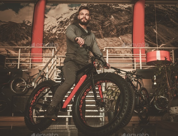 Handsome hipster man riding bike in bike showroom. - Stock Photo - Images