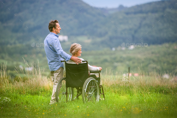 Senior man with woman in wheelchair, green autumn nature - Stock Photo - Images