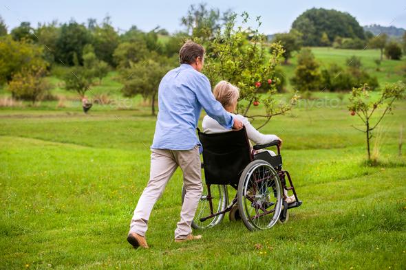 Senior man pushing woman in wheelchair, green autumn nature - Stock Photo - Images