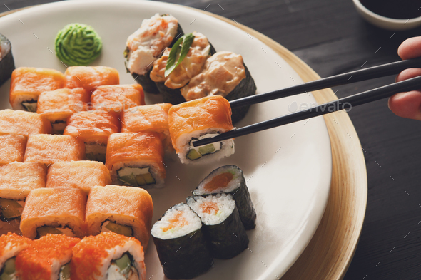 Eating sushi rolls at japanese food restaurant - Stock Photo - Images