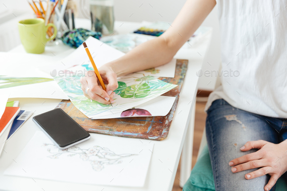 Woman painter drawing in art studio - Stock Photo - Images