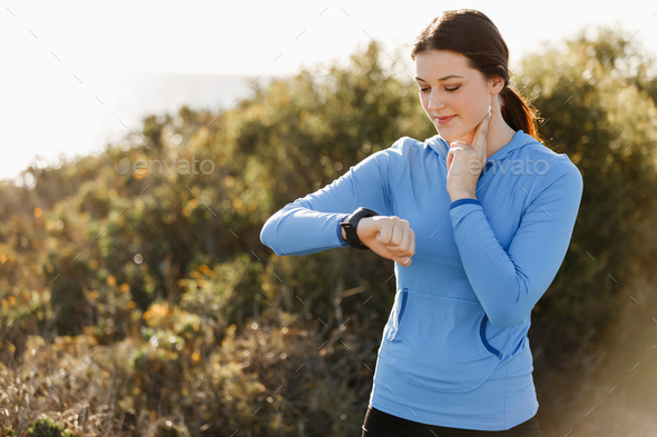 Runner woman with heart rate monitor running on beach - Stock Photo - Images
