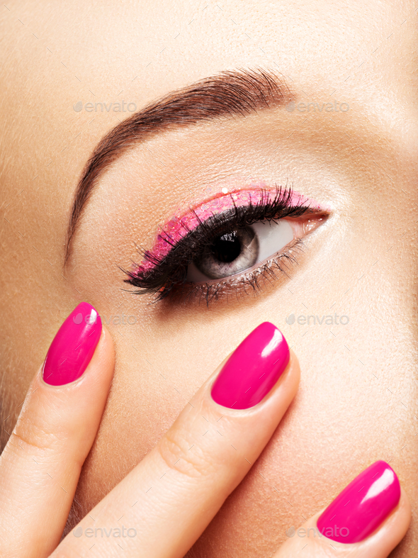 Closeup woman face with pink nails near eyes. - Stock Photo - Images