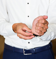 Business man fastening buttons on shirt sleeve at home close-up