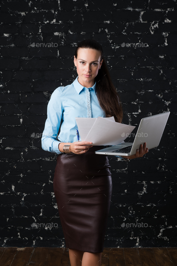 Businesswoman standing and holding laptop, front view.  - Stock Photo - Images