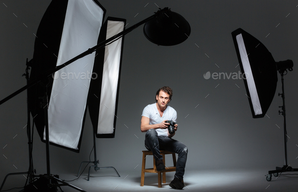 Man photograph sitting on the chair in professinal studio - Stock Photo - Images