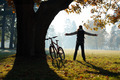 Excited woman cyclist standing in a park with hands outstretched - PhotoDune Item for Sale