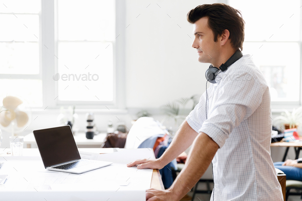Young man standing in creative office - Stock Photo - Images