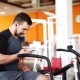 Man Listen To Music And Riding Stationary Bike In The Gym Chatting Cellphone - VideoHive Item for Sale