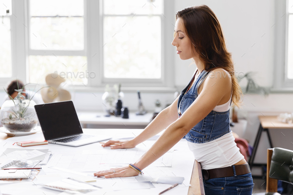 Young woman standing in creative office - Stock Photo - Images