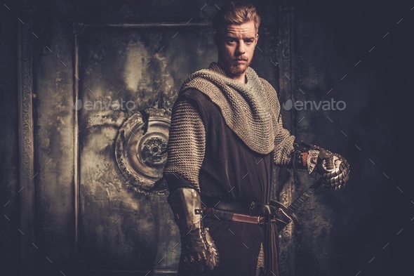 Young medieval knight standing on dark background. - Stock Photo - Images