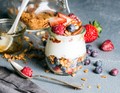 Yogurt oat granola with fresh berries, nuts, honey and mint leaves